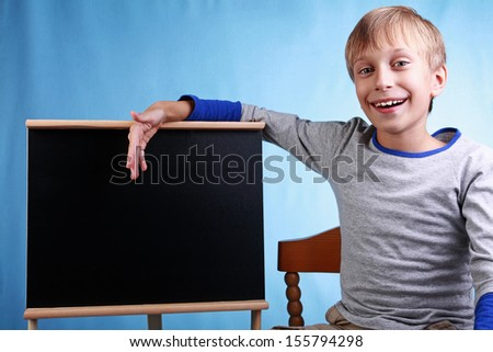Beautiful cheerful blond boy in a blue t-shirt smiles happily presenting a small clean blackboard    - stock photo
