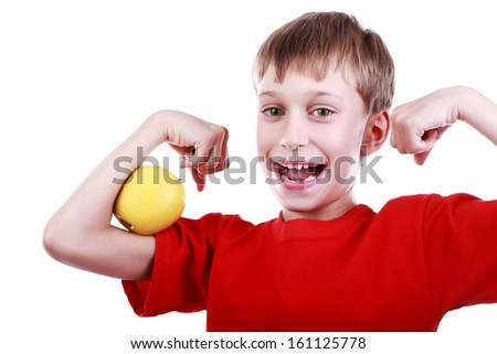 Beautiful cheerful blond boy in red t-shirt poses with apple and orange flexing his muscles and laughing  (isolated on white background) - stock photo