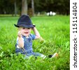 beautiful cheerful boy with black hat in summer park - stock photo