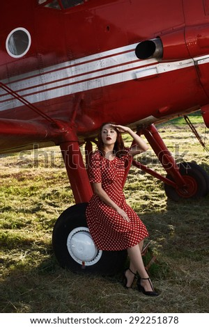beautiful cheerful brown haired pin-up lady with vintage haircut and red dress sits on airplane wheel in setting sun. The airplane is red and vintage and stands on sunlit grass.  - stock photo