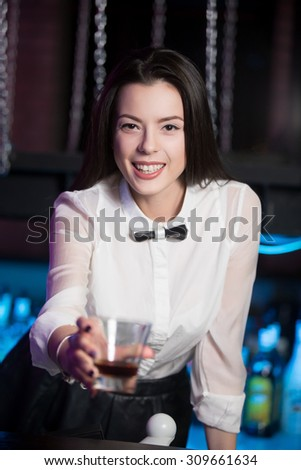 Beautiful cheerful brunette bartender girl in uniform white shirt and black bow tie, looking at camera, serving alcohol drink at nightclub bar, holding glass, offering drink - stock photo