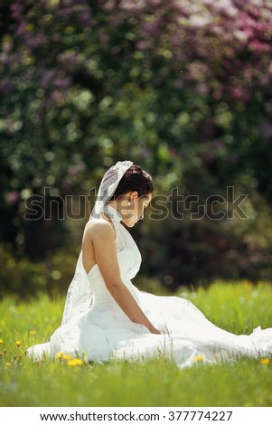 Beautiful cheerful brunette bride sitting & posing in meadow