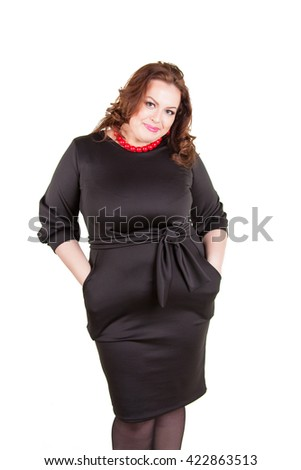 Beautiful cheerful busty brunette in a black dress standing isolated on white background
