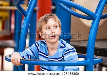 Beautiful cheerful child playing on a colorful playground climbing  - stock photo
