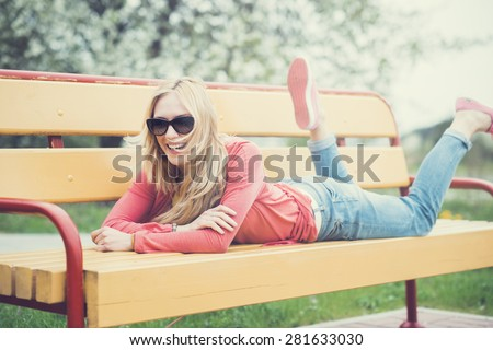 beautiful cheerful girl in sunglasses on a park bench - stock photo
