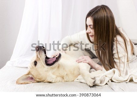 Beautiful cheerful girl plays with a yellow dog labrador retriever in a bed