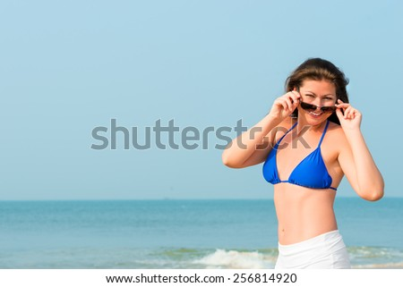 beautiful cheerful girl posing against a background of the sea - stock photo