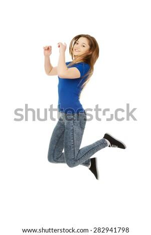 Beautiful cheerful jumping teen woman. - stock photo