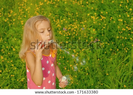 Beautiful cheerful little girl creates bubbles in summer green park.