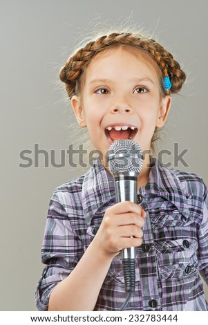Beautiful cheerful little girl singing into microphone, isolated on gray background. - stock photo