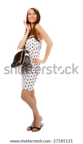 beautiful cheerful model poses in polka-dot dress with black bag on white