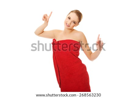 Beautiful cheerful spa woman pointing up. - stock photo