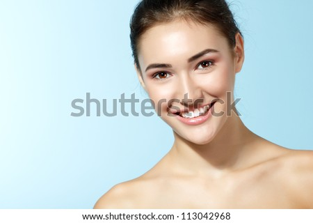 beautiful cheerful teen girl, beauty female face happy smiling and looking at camera over blue background - stock photo