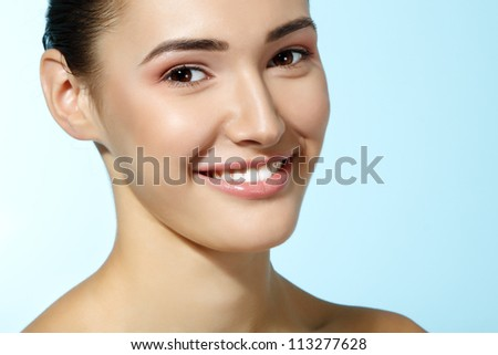 beautiful cheerful teen girl, beauty smiling female over blue background - stock photo