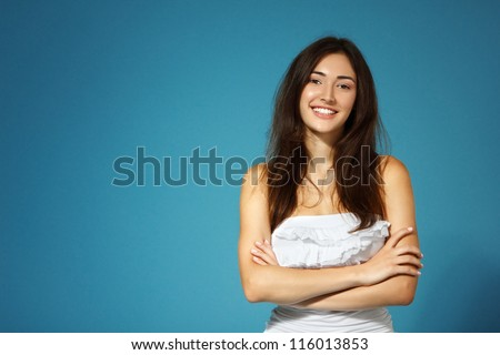 beautiful cheerful teen girl in white top over blue background