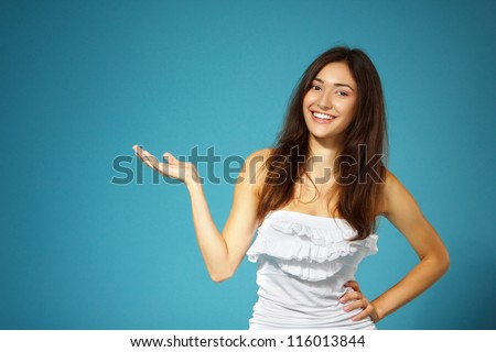beautiful cheerful teen girl show something with her hand over blue background - stock photo
