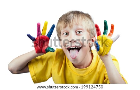 Beautiful cheerful white boy in yellow t-shirt showing painted hands with funny expression showing his tongue  - stock photo
