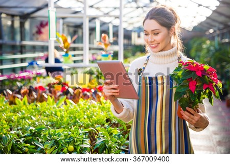 Beautiful cheerful woman gardener in apron using tablet and holding plant in pot with colorful leaves in garden center - stock photo