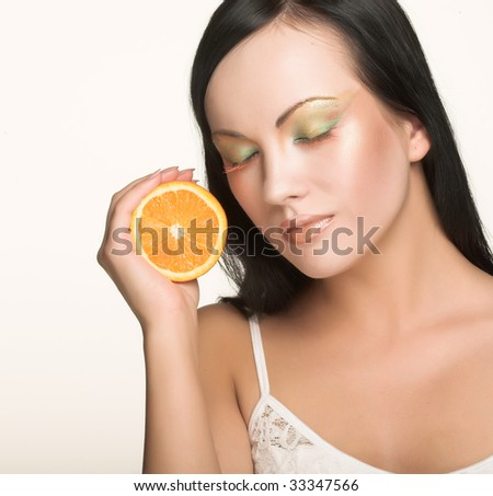 beautiful cheerful woman with fresh orange near her face