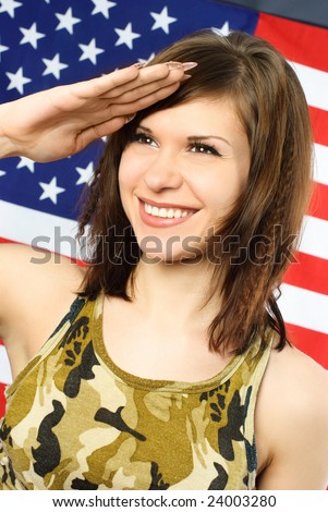 beautiful cheerful young woman dressed in camouflage salutes opposite an American flag