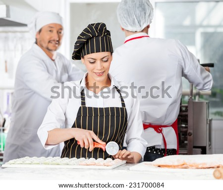 Beautiful chef cutting ravioli pasta at counter with colleagues working in background at commercial kitchen - stock photo