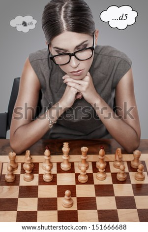 Beautiful chess player thinking, first move - stock photo