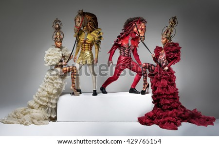 Beautiful chess queens with men in horse masks on podium - stock photo
