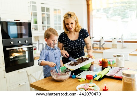 Beautiful child and mother baking in kitchen with love
