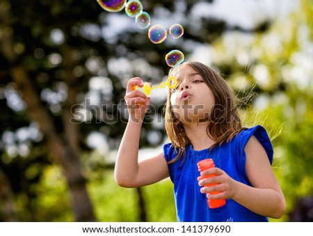 beautiful child blowing bubbles in a meadow  with greenery in the background - stock photo