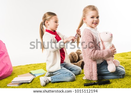 beautiful child brushing hair of sister while she sitting on floor with toy bunny isolated on white