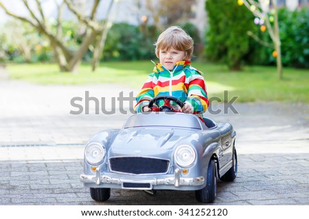Beautiful child driving big toy old vintage car and having fun, outdoors. Active leisure with kids outdoors  on warm spring or autumn day. - stock photo