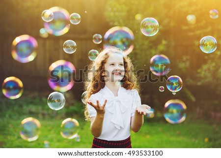 Beautiful child enjoying blowing soap bubbles in the summer on nature. Background toning instagram filter. Happy childhood concept.