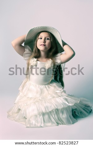 Beautiful child girl in white dress and hat. Portrait of elegant beautiful girl 10 years old. - stock photo
