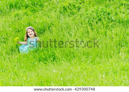 Beautiful child girl with dandelion flower in spring park. Happy kid having fun outdoors - stock photo