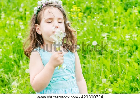 Beautiful child girl with dandelion flower in spring park. Happy kid having fun outdoors