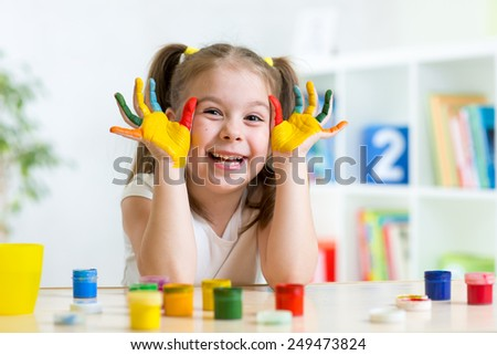 beautiful child girl with hands in color paints at home - stock photo