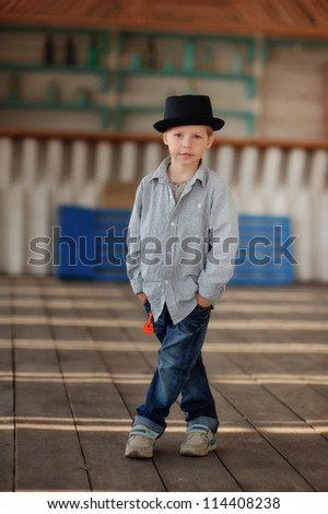 beautiful child in a black hat and jeans posing on a wooden floor - stock photo