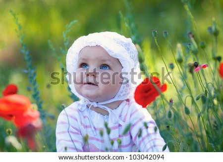 Beautiful child on the flower meadow - stock photo