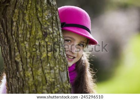 Beautiful child peeking behind a tree - stock photo