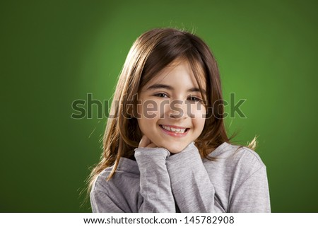 Beautiful child smiling into the camera, against a green background - stock photo