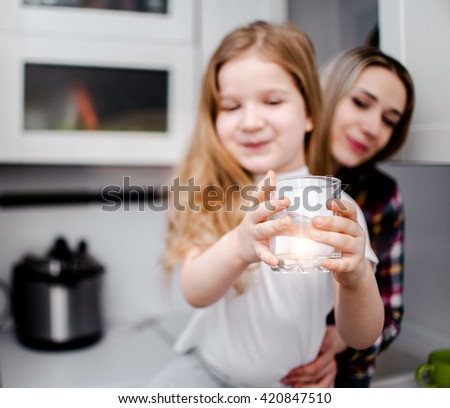 Beautiful child takes glass with water sitting near her nanny - stock photo