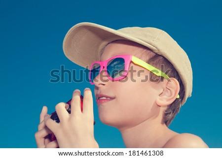 Beautiful child wearing colorful sunglasses with camera on beach - stock photo