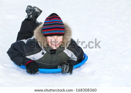 Beautiful child wearing winter clothes sledding on snow having fun  - stock photo