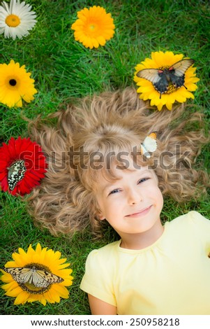 Beautiful child with butterfly in spring park. Happy kid lying on green grass outdoors - stock photo