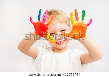 Beautiful child with hands in paint. Portrait of laughing playful kid. Close up of cheerful funny boy isolated on white background. Blond baby portrait ready to make hand prints. Education concept.  - stock photo