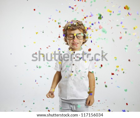 Beautiful child with rimmed glasses and confetti. Portrait of child wrapped with confetti - stock photo