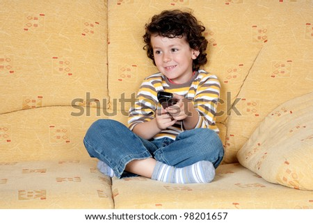 Beautiful child with the remote control of television sitting on the couch
