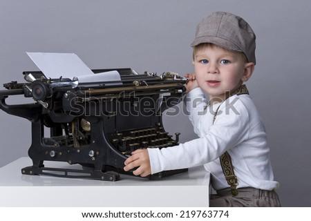 beautiful child with typewriter - stock photo