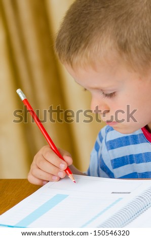 Beautiful  child writing with a red pen