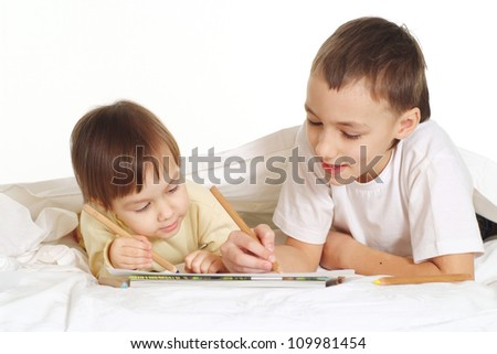 Beautiful children write in a notebook with a pencil on a white background